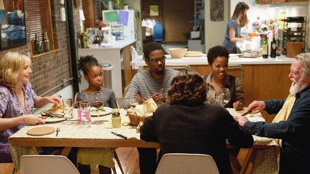 Sechs Personen sitzen an einem Tisch und Essen.