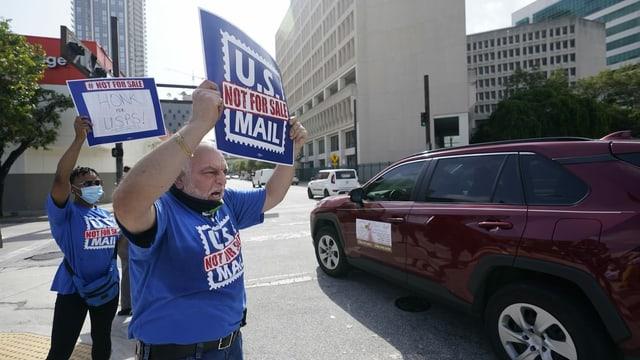 Zwei Personen demonstrieren mit Schildern gegen Änderungen bei der US-Post.