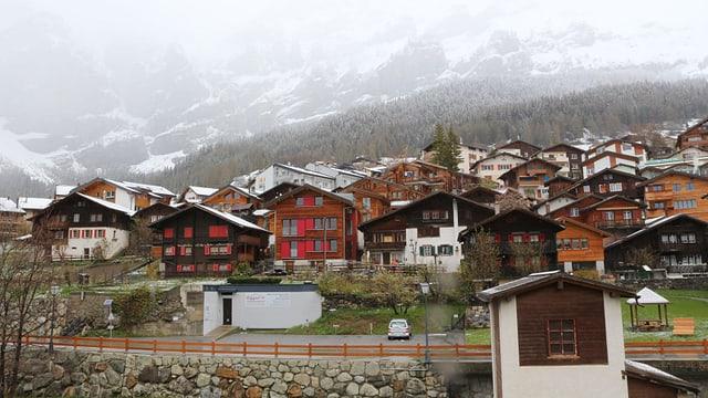 Ein Dorf mit verschneiten Bergen.