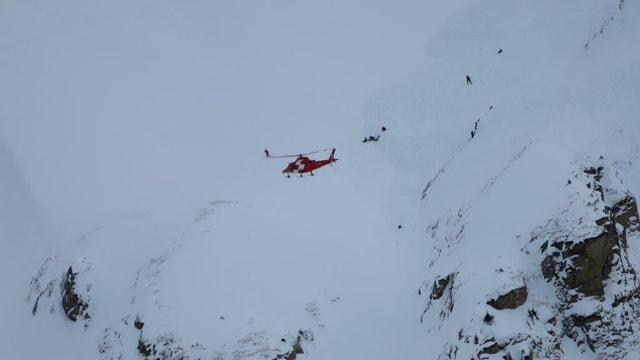 Felswand, Schnee, davor Rega-Helikopter.