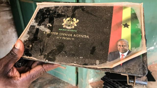 Ein Lehrer zeigt einen defekten Laptop, der einst von Ghanas Regierung gespendet wurde. Am Boden stehen noch weitere kaputte Computer.