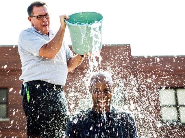 Ein Mann leert einem andern Mann Wasser aus einem Kübel auf den Kopf. Beide sehen vergnügt aus