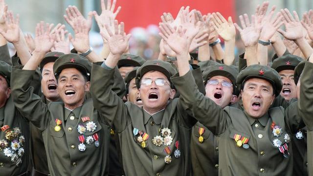 Uniformierte Soldaten winken begeistert.