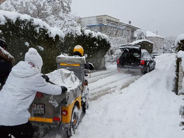 Pöstler auf tief verschneiter Strasse kämpft sich den Hügel hinauf.