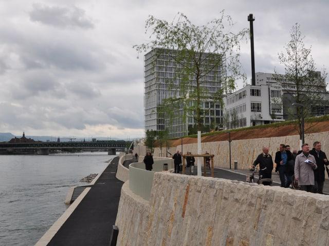 Menschen spazieren auf dem Rheinuferweg.