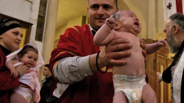 Zwei Kinder werden getauft.