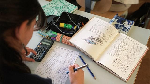Eine Jugendliche löst mit einem Taschenrechner ein Aufgabenblatt