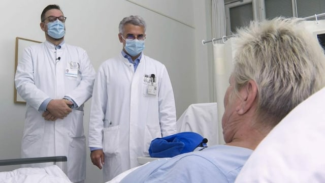 Zwei Ärzte am Spitalbett einer Patientin.