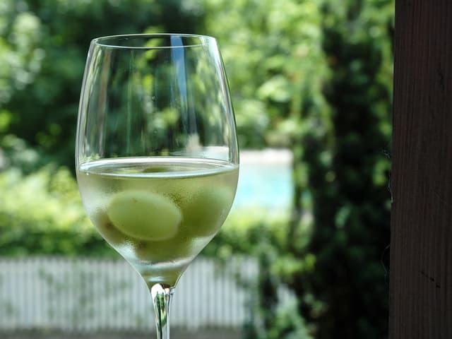 Weissweinglas mit Traubenbeeren drin auf dem Balkongeländer.
