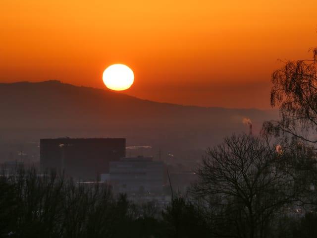 Sonne knapp über dem Horizont, orange-gelber Himmel