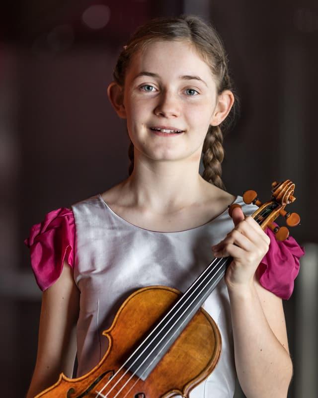 Ein Mädchen mit Zöpfen hält eine Geige in der Hand.