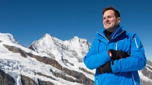 Ein Mann mit blauer Jacke steht vor einer verschneiten Bergkette.