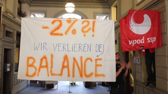 Ein weisses Transparent mit der Aufrschrift:« -2%?! Wir verlieren die Balance»