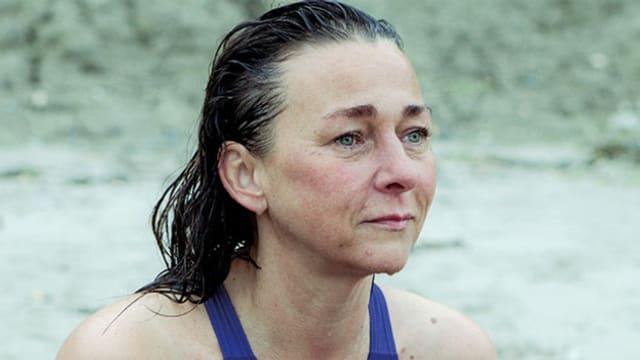 Porträt einer Frau im Badeanzug, die ins Leere blickt.