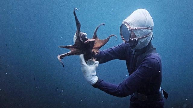 Eine Frau taucht im Meer auf der Suche nach Muscheln.