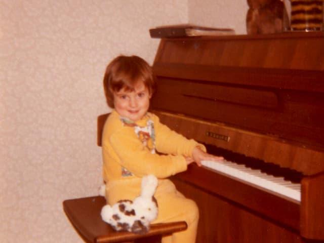 Kleines Mädchen mit Plüschhase sitzt an Klavier.