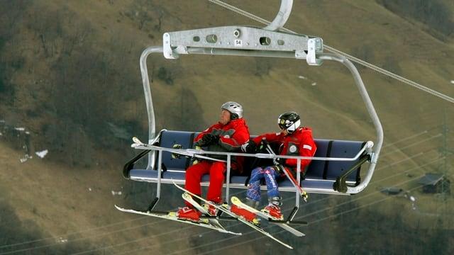 Skifahrer auf Sessellift vor grünen Wiesen