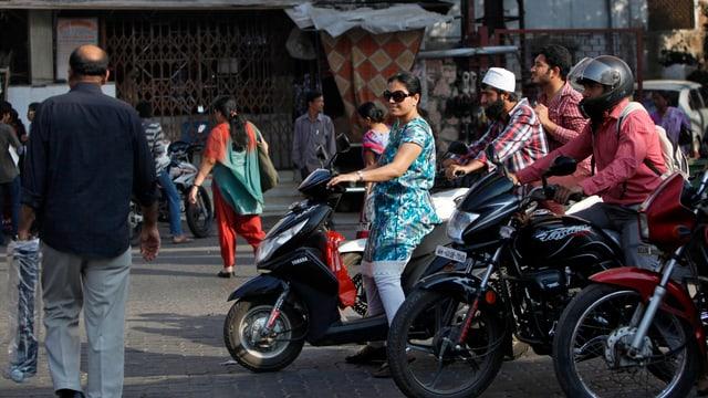 Männer und Frauen auf Rollern in Indien