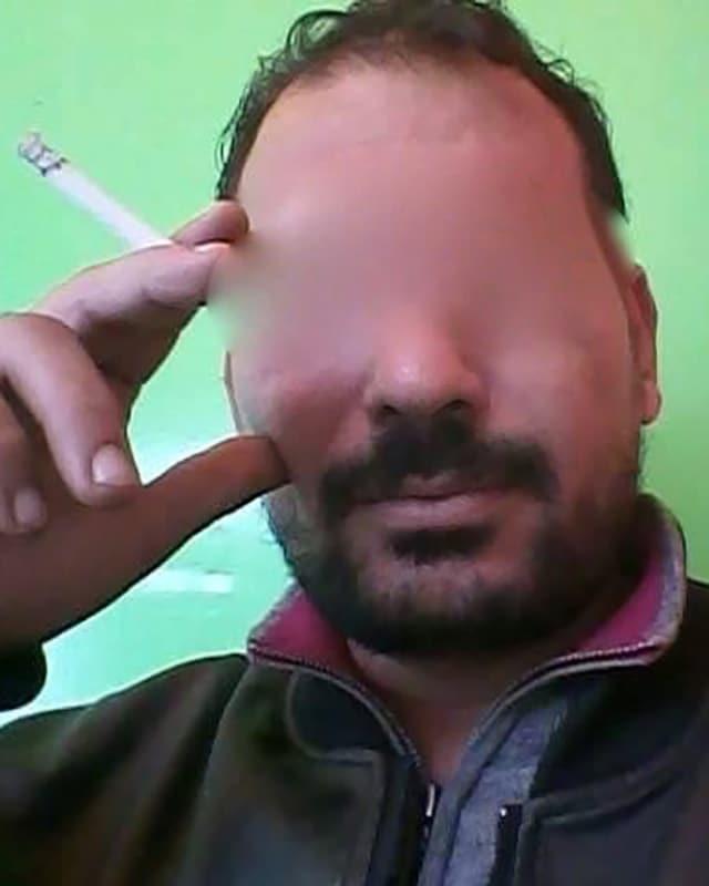 Ein bärtiger Mann mit Zigarette, dessen Augen verpixelt sind.