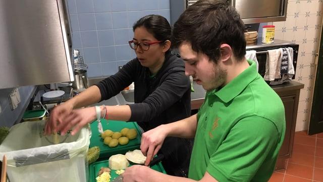 Ein Mann in einem grünen T-Shirt und eine Frau mit schwarzem T-Shirt schneiden Gemüse in einer Küche.