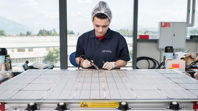 Eine Mitarbeiterin zerschneidet Komponenten für eine Photovoltaik-Anlage.