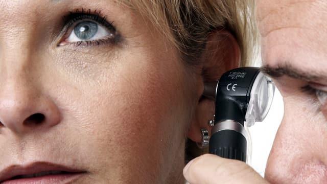 Arzt überprüft das Ohr einer Patientin