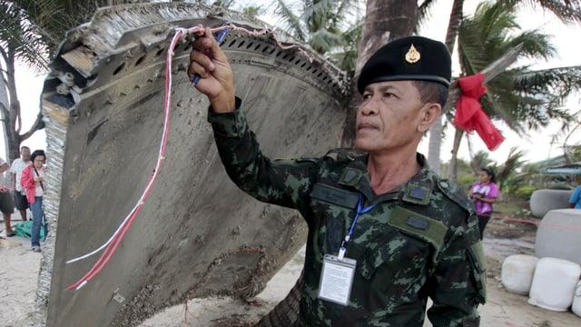 Asiatischer Armeeangehöriger untersucht Wrackteil