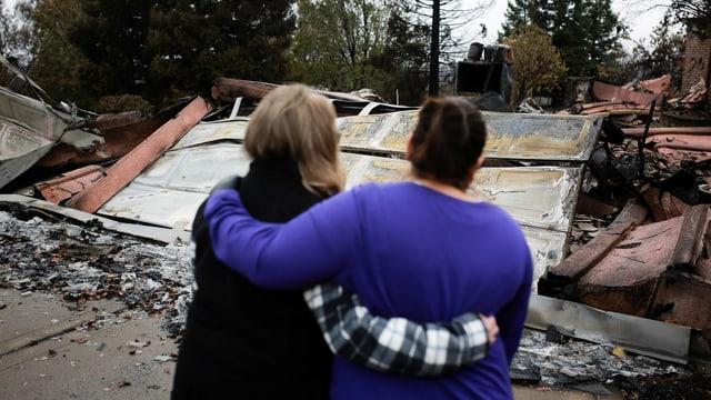 Zwei Frauen stehen Arm in Arm vor ihrem zerstörten Hab und Gut.