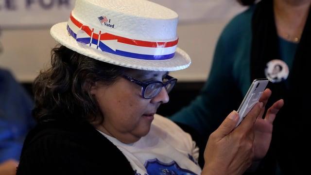 Eine Anhängerin der Demokraten schaut auf ihr Handy