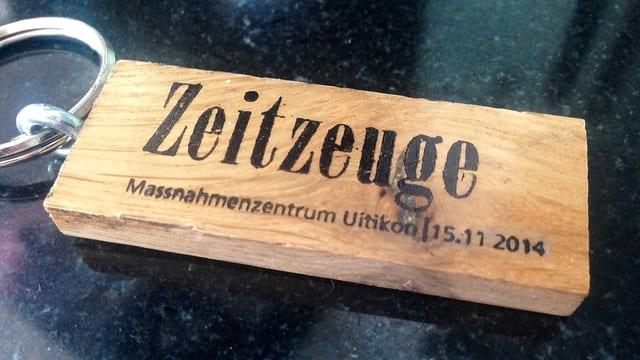 """Schlüsselanhänger aus Holz mit der Aufschrift """"Zeitzeuge - Massnahmenzentrum Uitikon/15.11.2014"""