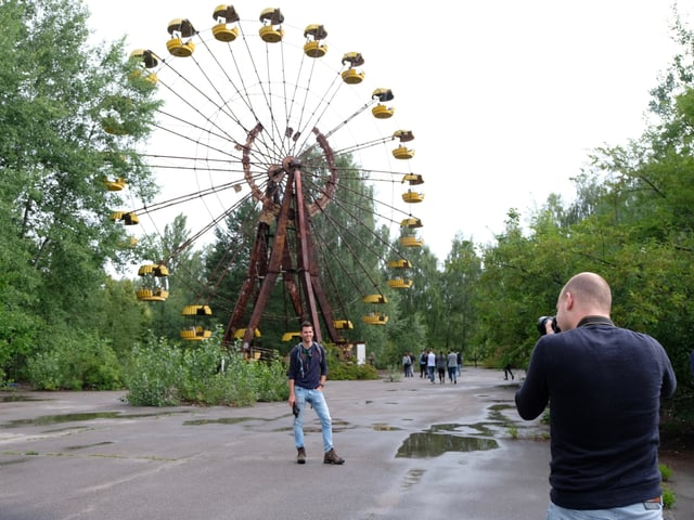 Mann macht Foto vor Riesenrad.