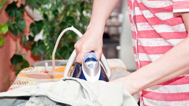 Eine Person bügelt Kleidung.