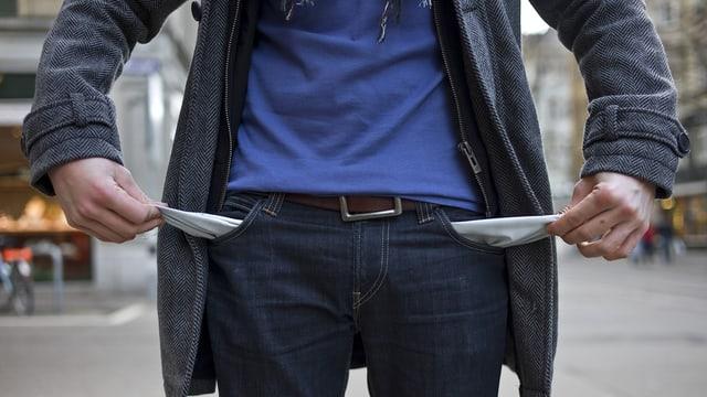 Ein Mann zeigt seine leeren Hosentaschen.