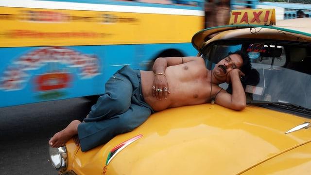 Taxifahrer schläft auf Kühlerhaube, Indien