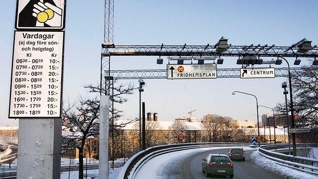 Eine Strasse in Stockholm, ein Schild weist auf die Gebühren hin, Messgeräte hängen über den Strassen.