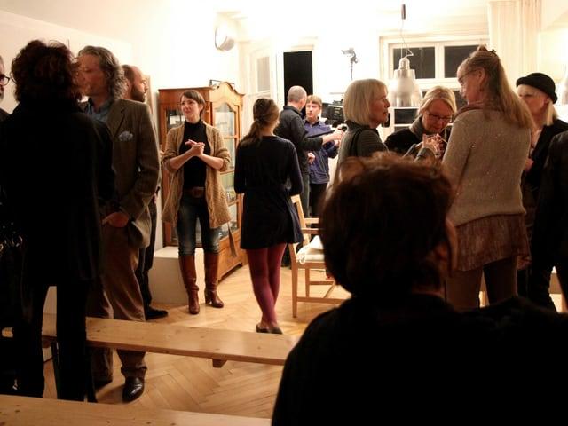 In einem Wohnzimmer stehen und sitzen viele Gäste.