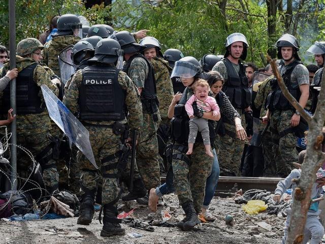 Eine mazedonische Polizistin hält ein Flüchtlings-Baby im Arm