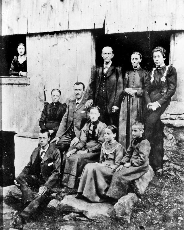 Altes Schwarzweissfoto: Gruppenbild einer grossen Familie vor einem Haus.