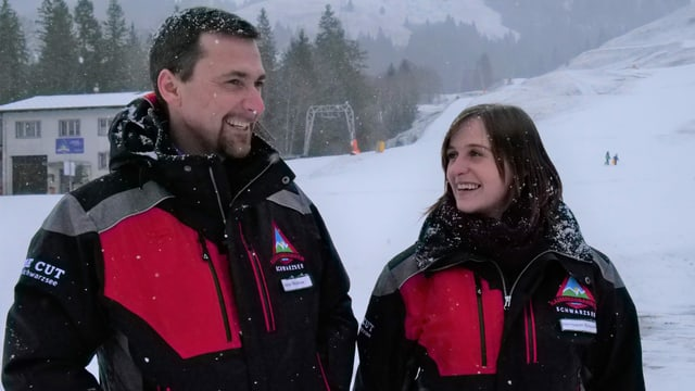 Zwei Personen lachen, während Schnee fällt.