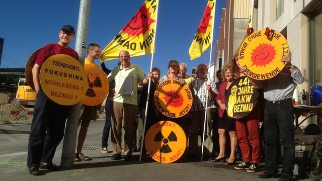 Mehrere Aktivisten stehen mit Anti-Atom-Plakaten und -Fahnen auf der Strasse.