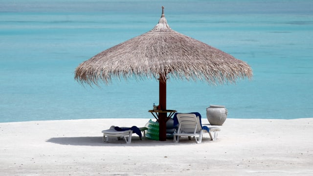Zwei Stühle stehen unter einem Sonnenschirm an einem Strand mit Blick aufs Meer.