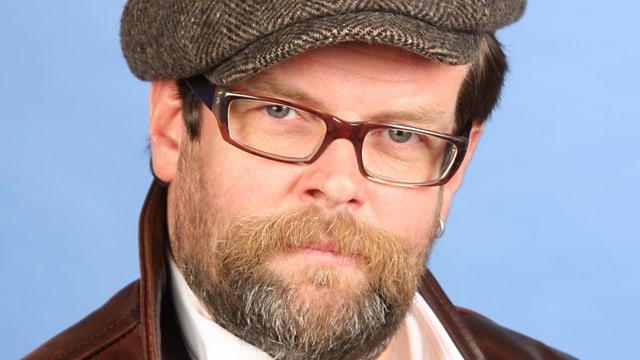 Der deutsche Kabarettist mit Bart, Brille und Mütze.
