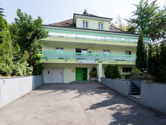 Blick auf ein grünlichen Haus mit grosser Einfahrt. Das Haus steht in einem grünen Wohnquartier.