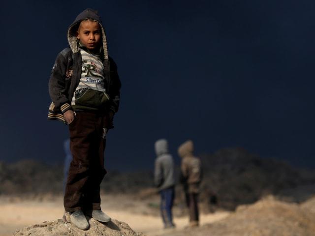 Kinder in Mosul vor brennenden Ölfeldern.