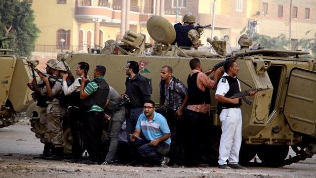 Sicherheitskräfte verstecken sich hinter einem Panzer während einer Schiesserei mit mutmasslichen Militanten.