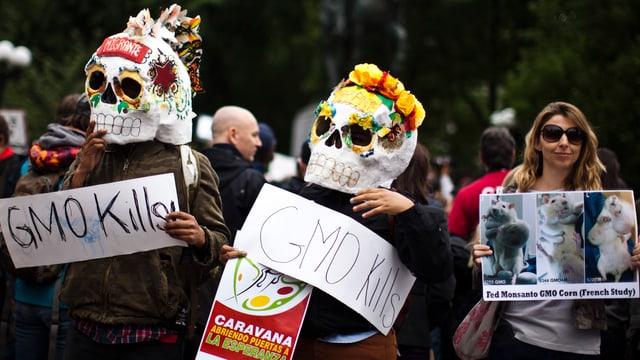 Kostümierte Demonstranten tragen Transparente
