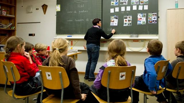 Schulkinder konzentrieren sich auf die Lehrerin an der Tafel.
