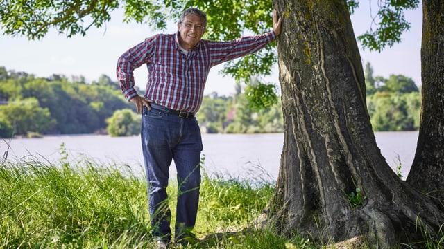 ein Mann steht in der Natur und stützt sich an einem Baum ab
