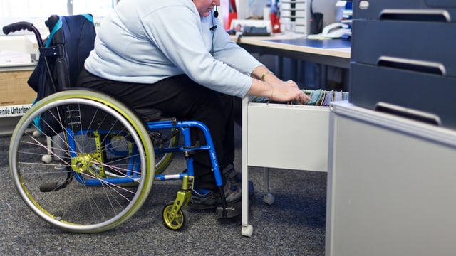 Eine Person im Rollstuhl arbeitet in einem Büro.