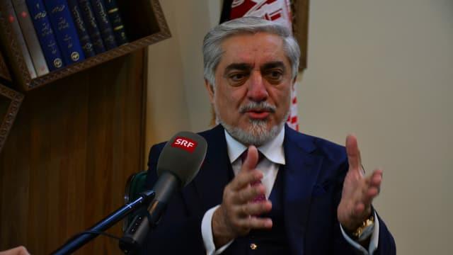 Abdullah spricht in ein SRF-Mikrofon und gestikuliert mit den Händen.